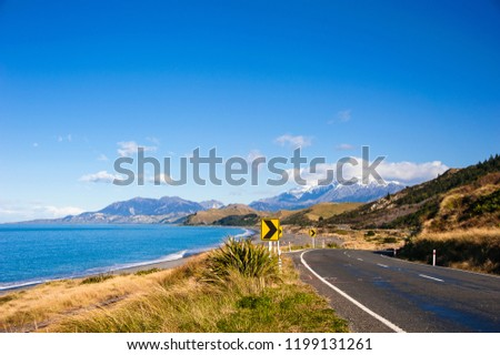 State Highway 1, iconic coastal route near Kaikoura, New Zealand, considered to be one of the top coastal drives in the world. Snow capped mountains meet sea, sky and road. Royalty-Free Stock Photo #1199131261