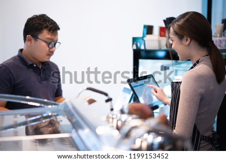 Customers are ordering food workers are using computers. #1199153452