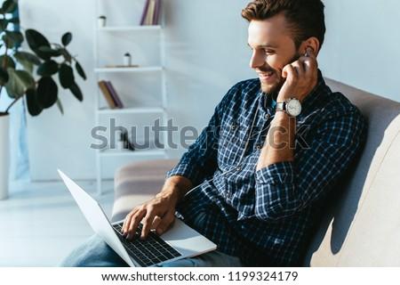 side view of smiling man in earphones taking part in webinar at home #1199324179