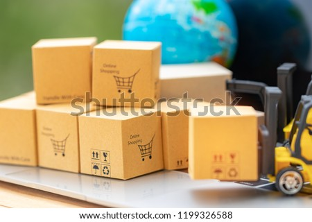 Mini forklift truck load cardboard box with symbols on laptop keyboard and globe nearby with soft focus. Logistics and transportation management ideas and Industry business commercial concept. #1199326588