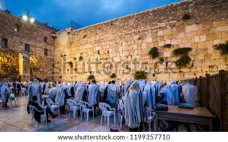 Orthodox Jewish men in Tallit prayer shawls standing from before dawn for Shacharit sunrise prayer at the Western/Wailing Wall or Kotel, the holiest place in Judaism; Jerusalem Israel #1199357710