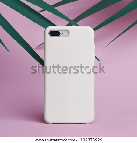 mock up of smart phone on a pink background of palm leaves in a white plastic case back view. Template of phone case for iPhone 8 plus #1199375926