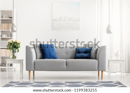 Blue pillows on grey couch next to table with flowers in white flat interior with painting. Real photo #1199383255
