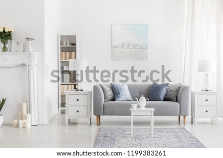 White table on carpet in front of grey settee in apartment interior with painting and lamp. Real photo #1199383261