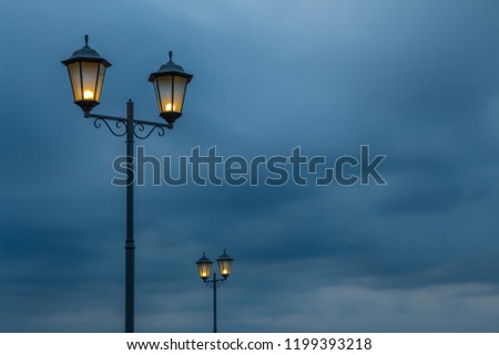 Two beautiful metal streetlights on cloudy dark blue sky background. A row of vintage street posts with lighting two lamps on each. Place space for your text. #1199393218