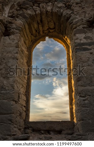 Beautiful colorful clouds on blue sky on sunset. View through arched window in old stone abandoned church. Аrchitecture concept. #1199497600