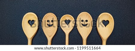 Kitchen wooden spoons with smile and heart on gray top table. Wooden kitchen tools and utensils, close up banner