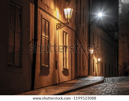 Narrow cobbled street illuminated by street lamps of Old Town, Prague, Czech Republic. #1199523088