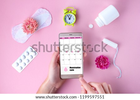 Tampon, feminine, sanitary pads for critical days, feminine calendar, alarm clock, pain pills during menstruation and a pink flower on a pink background. Care of hygiene during menstruation.  #1199597551