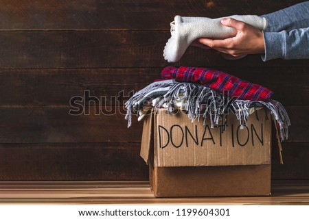 Donation concept. Donation box with donation clothes on a wooden background. Charity. Helping poor and needy people. Copy space  #1199604301