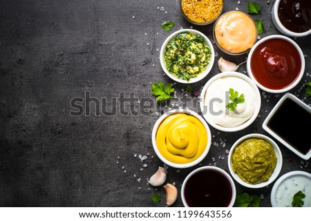 Set of sauces - ketchup, mayonnaise, mustard soy sauce, bbq sauce, pesto, chimichurri, mustard grains and pomegranate sauce on dark stone background. Top view copy space. #1199643556