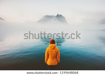 Woman alone looking at foggy sea traveling adventure lifestyle outdoor solitude sad emotions winter down jacket clothing cold scandinavian minimal landscape #1199648068