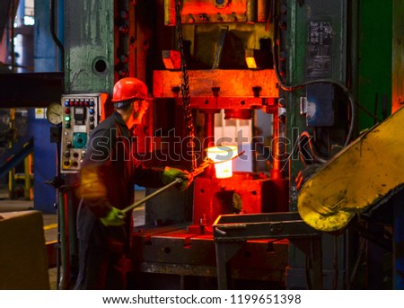 Blacksmith processes the red hot iron under a huge press. Metal forging, stamping under hammer forge at workshop of forge foctory. Blacksmithing, metallurgical, steelmaking, hot rolling mill #1199651398