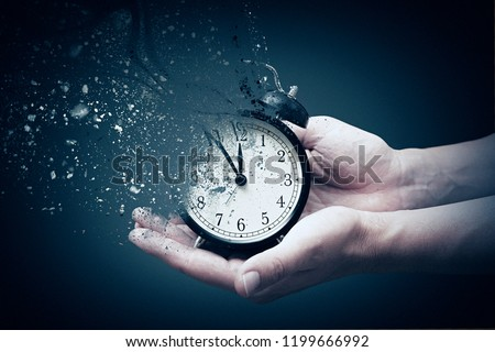 Concept of passing away, the clock breaks down into pieces. Hand holding analog clock with dispersion effect #1199666992