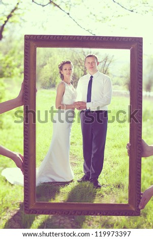 Portrait of the bride and groom are posing with the big frame in the park.
