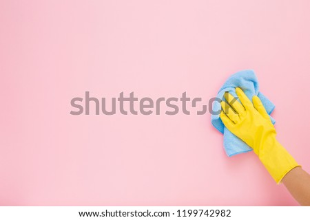 Employee hand in yellow rubber protective glove wiping pastel pink wall from dust with blue dry rag. General or regular cleanup. Commercial cleaning company. Copy space. Empty place for text or logo. #1199742982