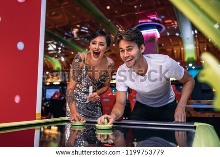 Couple playing air hockey game holding strikers at a gaming parlour. Excited man and woman having fun playing games at a gaming arcade. #1199753779