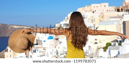 Traveler girl enjoying Santorini view with open arms and hat in the hand. Banner panorama. #1199783071