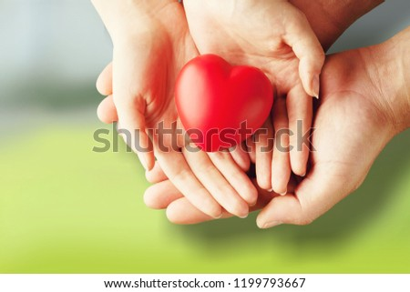 Adult and child hands holding red heart #1199793667