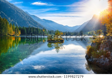 autumn sunset of Hintersee lake. Beautiful scene of trees near turquoise water of Hintersee lake.
