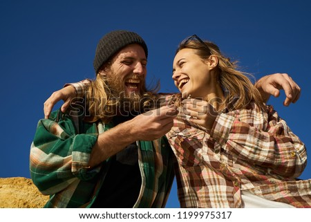 Laughing couple of friends hipsters passing a joint and hugging in blue sky background