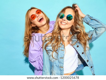 Two young beautiful blond smiling hipster girls in trendy summer clothes. Sexy carefree women posing near blue wall in sunglasses. Positive models #1200025678