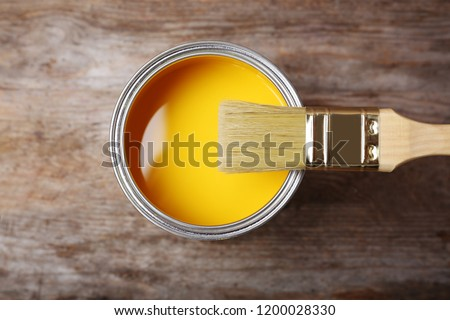Can with yellow paint and brush on wooden background, top view #1200028330
