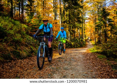Mountain biking woman and man riding on bikes at sunset mountains forest landscape. Couple cycling MTB enduro flow trail track. Outdoor sport activity. #1200070981