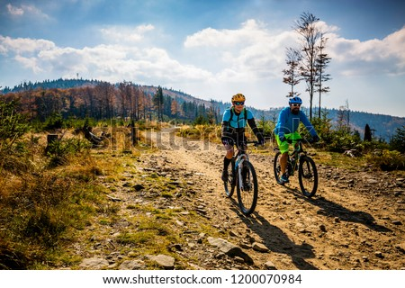 Mountain biking woman and man riding on bikes at sunset mountains forest landscape. Couple cycling MTB enduro flow trail track. Outdoor sport activity. #1200070984