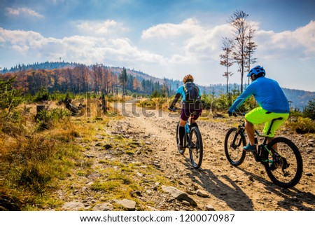 Mountain biking woman and man riding on bikes at sunset mountains forest landscape. Couple cycling MTB enduro flow trail track. Outdoor sport activity. #1200070987