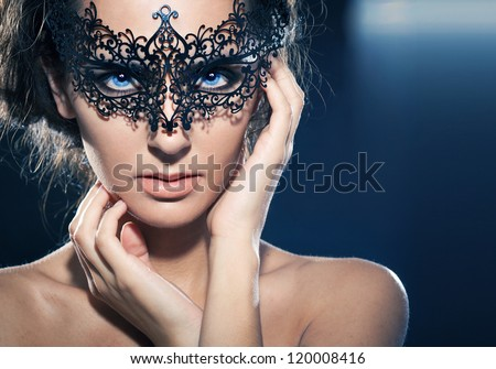 Mask.Nude.Girl.Venice carnival mask Close-up female portrait.Blue eyes. Black background
