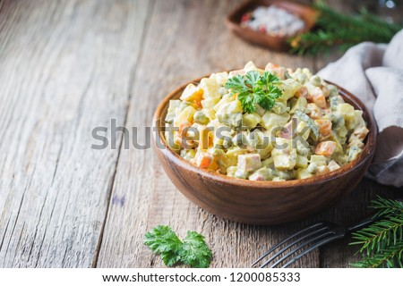 Traditional Russian salad with cooked vegetables with mayonnaise in a bowl. Wooden background. #1200085333
