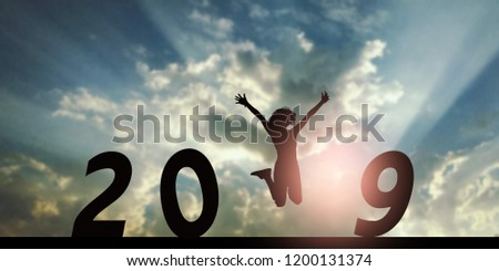 Newyear 2019 concept Silhouette young woman jumping to 2019 new year #1200131374