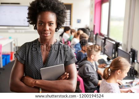 Portrait Of Female Teacher Holding Digital Tablet Teaching Line Of High School Students Sitting By Screens In Computer Class #1200194524