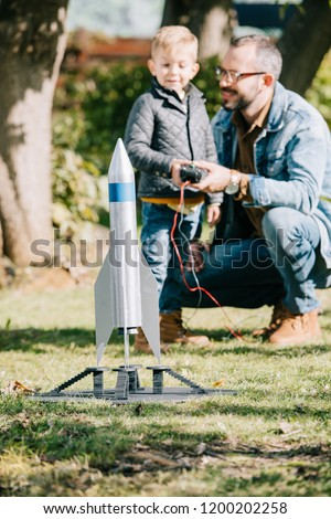 close-up view of model rocket and father with son playing behind #1200202258
