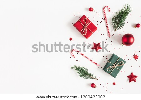 Christmas composition. Gifts, fir tree branches, red decorations on white background. Christmas, winter, new year concept. Flat lay, top view, copy space Royalty-Free Stock Photo #1200425002