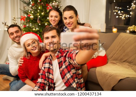 celebration and holidays concept - happy friends with glasses celebrating christmas at home party and taking selfie by smartphone #1200437134