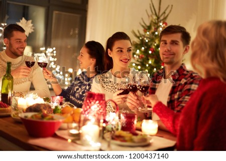 winter holidays and people concept - happy friends celebrating christmas at home feast and drinking red wine #1200437140
