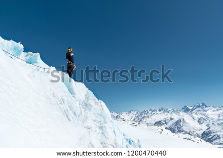The mountaineer stands on the edge of the glacier with a snow shovel in his hands and shows Shak's gesture against the blue sky and the Caucasus Mountains #1200470440