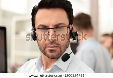 Group of business colleagues with headsets using computers at office desk #1200524956