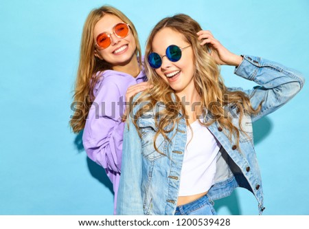 Two young beautiful blond smiling hipster girls in trendy summer clothes. Sexy carefree women posing near blue wall in sunglasses. Positive models going crazy #1200539428
