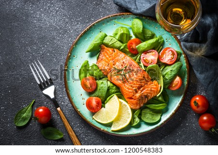 Baked salmon fish fillet with fresh salad from spinach and tomatoes on black stone table. Top view copy space. #1200548383