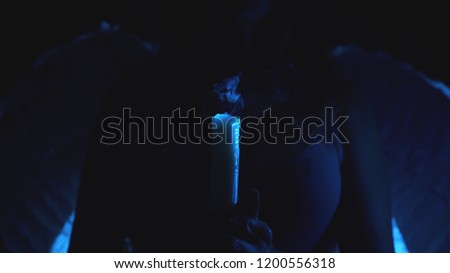 silhouette of a woman with angel wings, holding a candle in her hands. blow off the flame of the candle, the smoke from the wick of the candle in the dark. against the background of angelic wings. #1200556318
