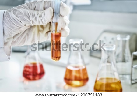 The scientist test the natural product extract, oil and biofuel solution, in the chemistry laboratory. sepia or retro tone #1200751183