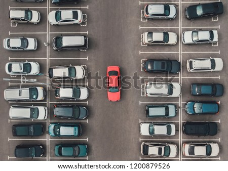 Top view of the crowded Parking lot with quadcopter or drone. Original bright automobile among the grey of mediocre cars. Parking space search, No parking space. #1200879526