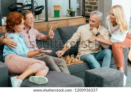happy mature friends gathering together and playing chess at home #1200936337