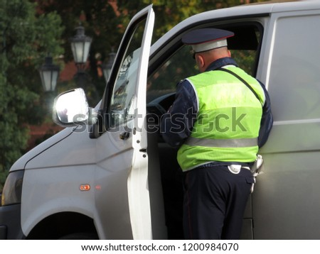 Traffic police officer checks the documents of the car driver. Policeman on the road, traffic cop, concept for violation of traffic rules, road accident #1200984070