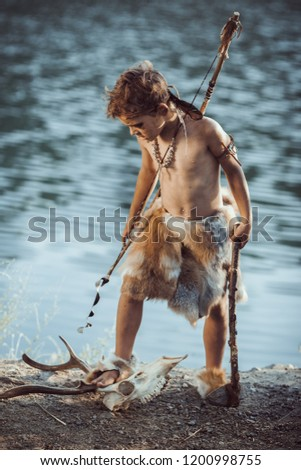 Angry caveman, manly boy with stone axe and bow hunting near river. Prehistoric tribal boy outdoors on nature. Young shaggy and dirty savage, warrior and hunter with weapon. Primitive ice age man in #1200998755