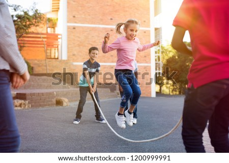 Happy elementary kids playing together with jumping rope outdoor. Children playing skipping rope jumping game and laughing outdoors. Happy cute girl jumping over skipping rope held by her friends. Royalty-Free Stock Photo #1200999991