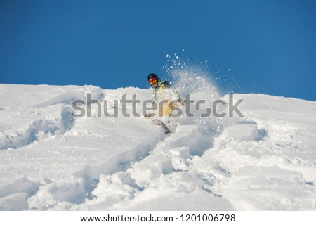 Snowboarder in bright sportswear riding down a snowy powder hill on bright sunny winter day against the sky #1201006798